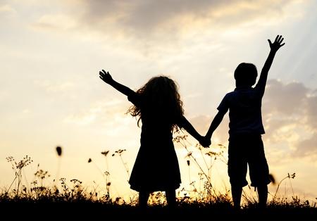 ni�os felices: Silueta, grupo de ni�os felices jugando en el prado, puesta de sol, verano