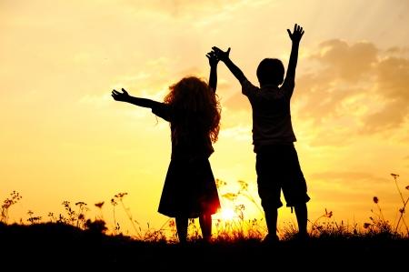 Silhouette, de groep van gelukkige kinderen die spelen op de weide, zonsondergang, zomer