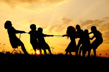 Silhouette, group of happy children playing on meadow, sunset, summertime Stock Photo - 10873900
