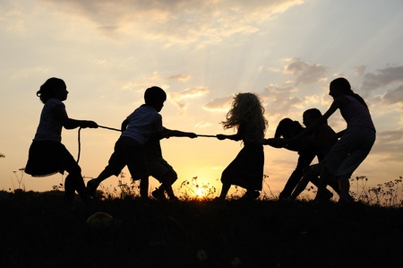 Silhouette, group of happy children playing on meadow, sunset, summertime Stock Photo - 10873848