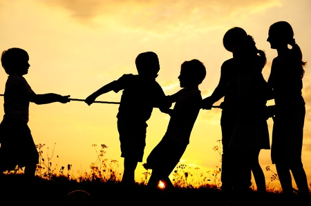 Silhouette, group of happy children playing on meadow, sunset, summertime Stock Photo - 10873943