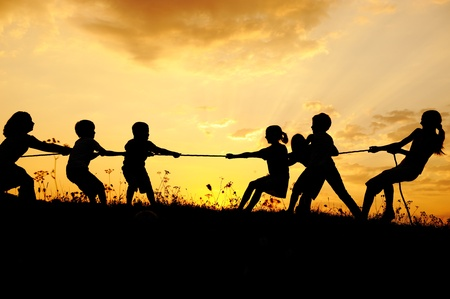 pulling beautiful: Silhouette, group of happy children playing on meadow, sunset, summertime