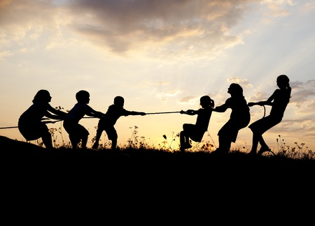 summertime: Silhouette, group of happy children playing on meadow, sunset, summertime