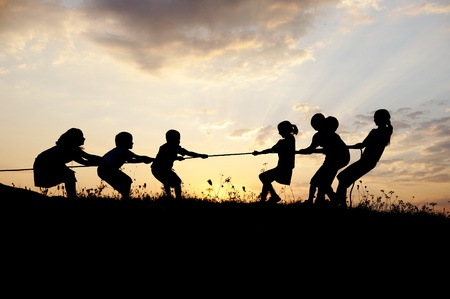 Silhouette, group of happy children playing on meadow, sunset, summertime Stock Photo - 10873917