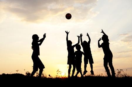 terrain de handball: Silhouette, un groupe d'enfants heureux de jouer sur la prairie, coucher de soleil, l'�t�