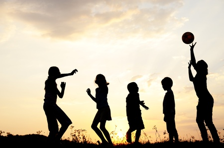 Silhouette, group of happy children playing on meadow, sunset, summertime Stock Photo - 10873918