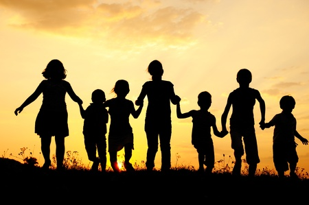Silhouette, group of happy children playing on meadow, sunset, summertime Stock Photo - 10873921