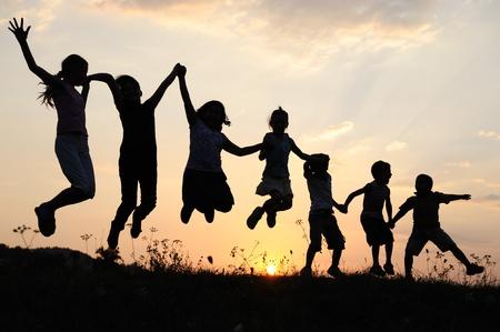 Dzieci: Sylwetka, grupa szczęśliwych dzieci bawiące się na łące, sunset, lato