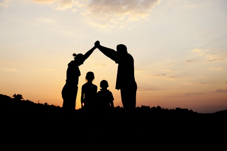 Silhouette, group of happy children playing on meadow, sunset, summertime Stock Photo - 10873796