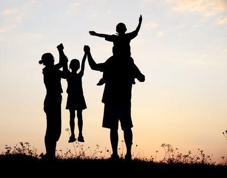 Silhouette, happy children with mother and father, family at sunset, summertime photo