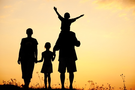 mama e hijo: Silueta, ni�os felices con la madre y el padre de la familia, al atardecer, durante el verano Foto de archivo