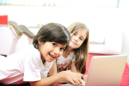 Little girl and boy lying with laptop at home on the ground Stock Photo - 11176645