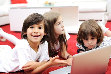 Three children lying with laptop at home on the ground photo