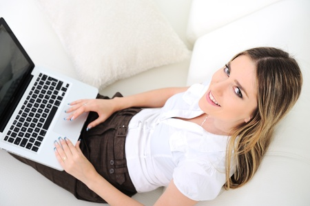 Young beautiful woman using laptop on sofa photo