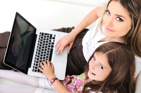 madre con hija: Madre e hija en el sof� con el port�til