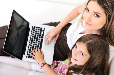 Mother and daugther with laptop on sofa photo