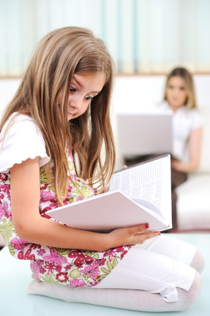 literacy: Little girl reading in home, indoor with happy family Stock Photo
