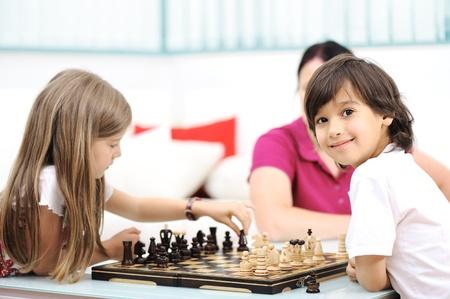 jugando ajedrez: Hermano y hermana jugando al ajedrez en casa con su madre