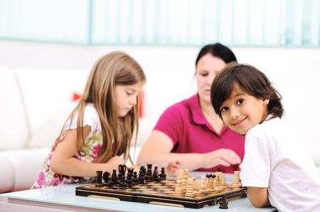 board games: Little brother and sister playing chess at home with their mother