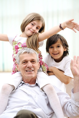 Grandfather with children, senior man at home with family photo