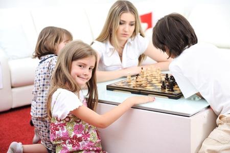 jugando ajedrez: Familia feliz en su casa, la madre de los j�venes jugando al ajedrez con sus hijos