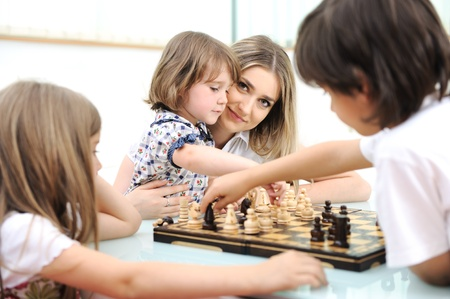 Happy family at home, young mother playing chess with her children photo