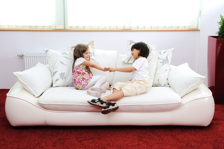 family on couch: Children at new home with modern furniture