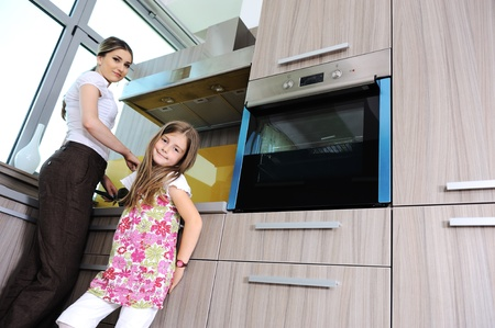 Mother and daughter preparing food in kitchen photo