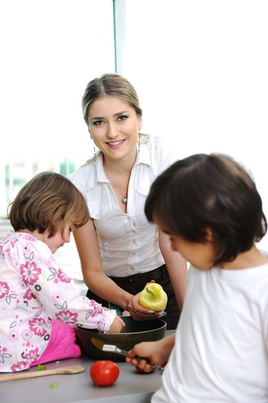 Happy children with their mother in the kitchen together photo