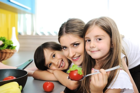 fun at work: Happy children with their mother in the kitchen together Stock Photo