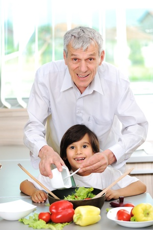 Grandfather and little boy in kitchen cooking together photo