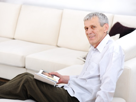 Elderly man relaxed, reading book  in living room Stock Photo - 11176669