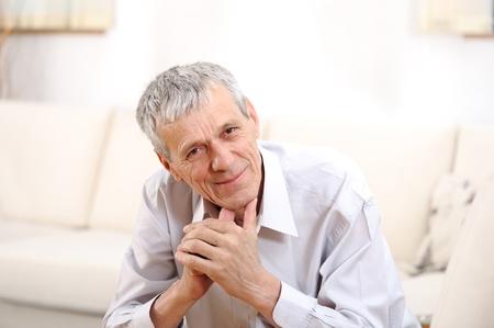 Happy relaxed elderly  man on sofa photo