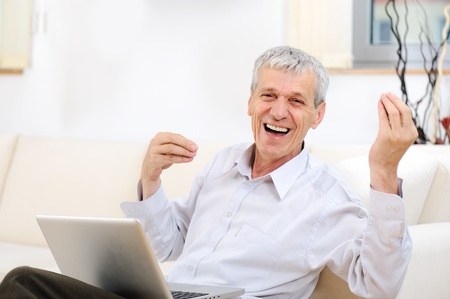 silver surfer: Senior good looking man with laptop at home