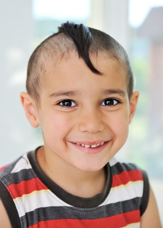 Cute little boy with funny hair and cheerful grimace photo