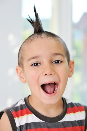 Cute little boy with funny hair and grimace photo