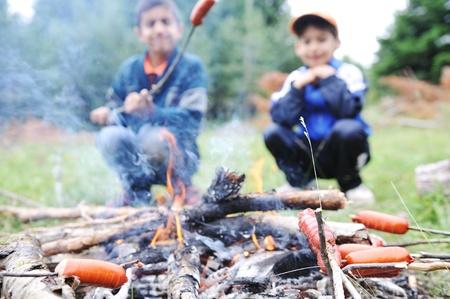 kinder: Barbecue in natura, un gruppo di persone preparazione salsicce sul fuoco (nota: dof poco profondo)