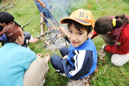 acampar: Barbacoa en la naturaleza, un grupo de niños embutidos en la preparación de fuego
