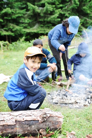 kinder: Barbecue in nature, group of children  preparing sausages on fire