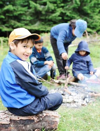 acampar: Barbacoa en la naturaleza, un grupo de niños que se preparan salchichas en el fuego