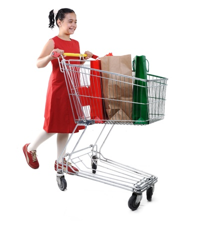 spending full: Little girl shopper in red dress with shopping cart Stock Photo