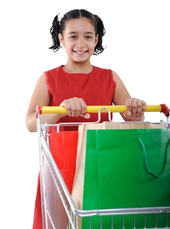 reduced value: Little girl shopper in red dress with shopping cart Stock Photo