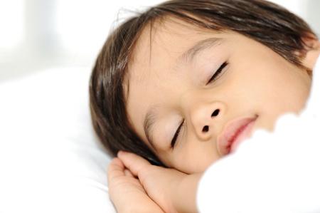sweet dreams: Kid on sleeping bed, happy bedtime in white bedroom