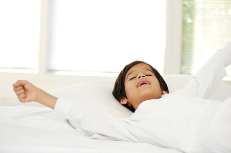 Kid on sleeping bed, happy bedtime in white bedroom photo