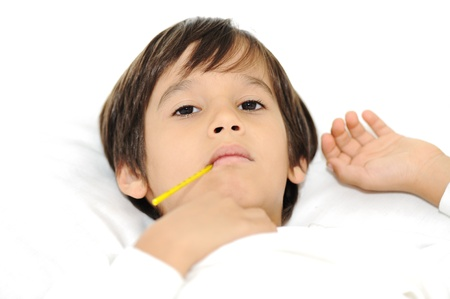 teen boy face: Sick little boy with thermometer, laying on bed