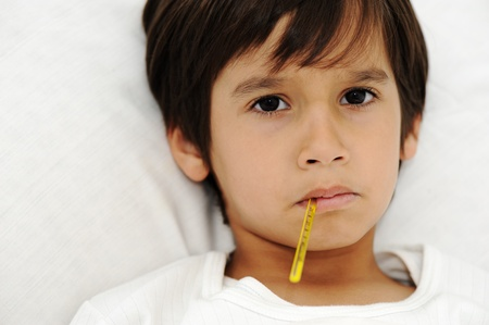 caucasian fever: Sick little boy with thermometer, laying on bed
