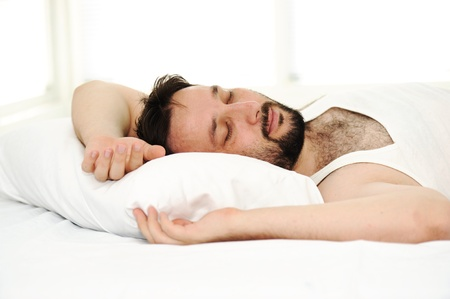 Man in sleeping bed, morning time photo