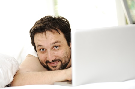 Man in sleeping bed using  laptop photo