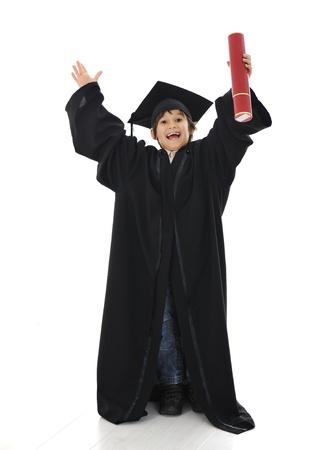 toga y birrete: Diploma de graduación niño pequeño alumno, la escuela primaria con éxito Foto de archivo
