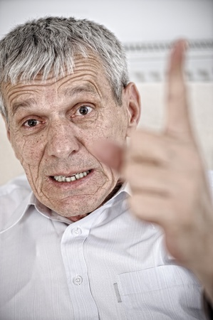 Angry senior man pointing his finger photo